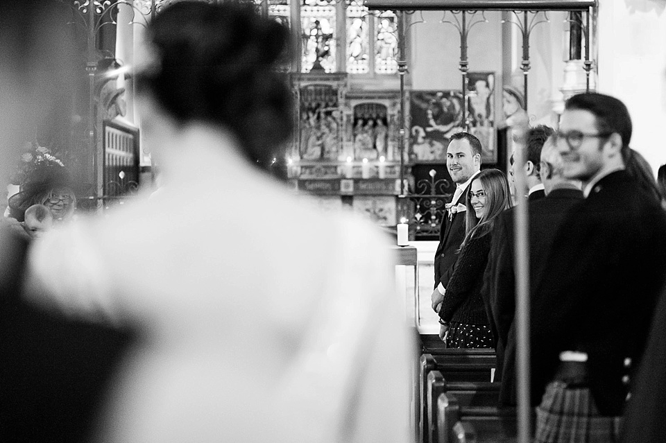 Groom watching bride walk down the aisle in black and white - natural wedding photography by Fiona Kelly