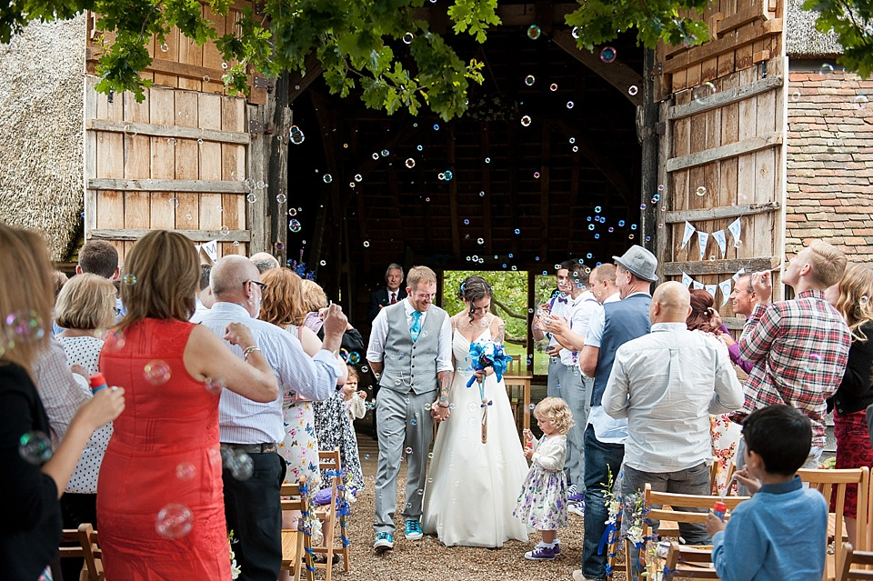 Bubbles alternative to confetti shot - bride with bright blue bouquet and groom in waistcoat and blue tie at Kent barn wedding venue england - natural wedding photography by Fiona Kelly
