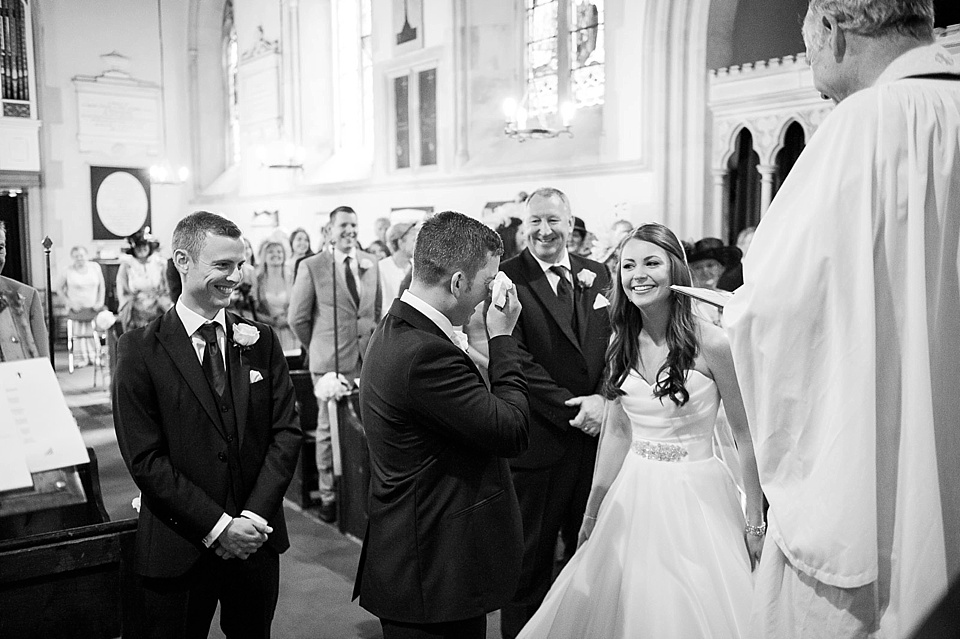 Emotional groom in church wedding ceremony - natural wedding photography by Fiona Kelly