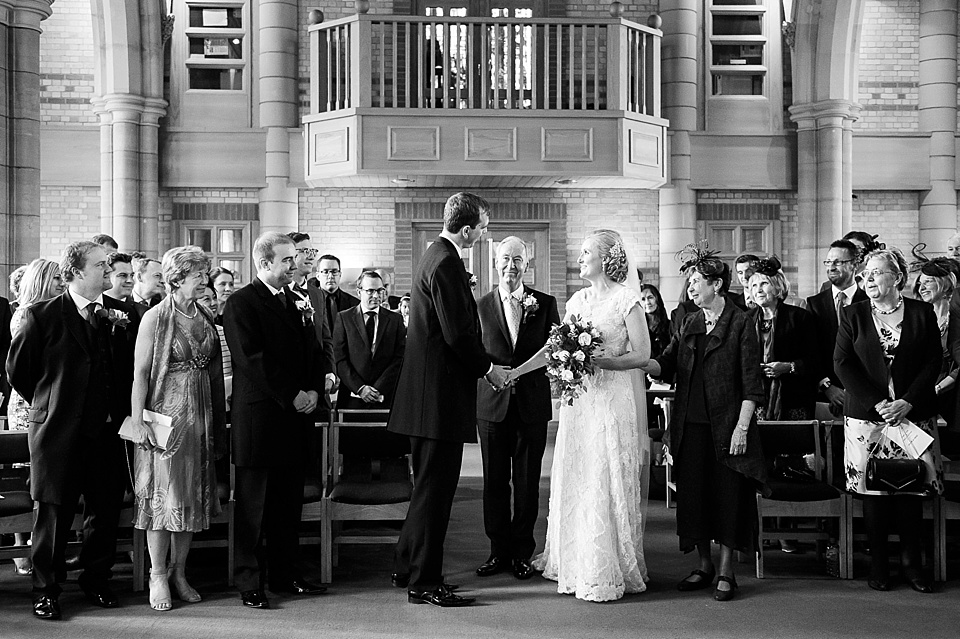 Bride stands holding groom's hand with father of the bride - natural wedding photography by Fiona Kelly