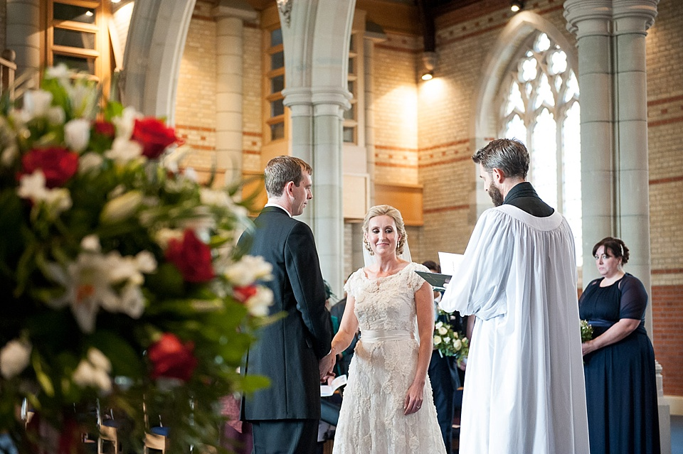 Bride in lace dress standing with groom and vicar in church wedding ceremony and red and white flowers - natural wedding photography by Fiona Kelly