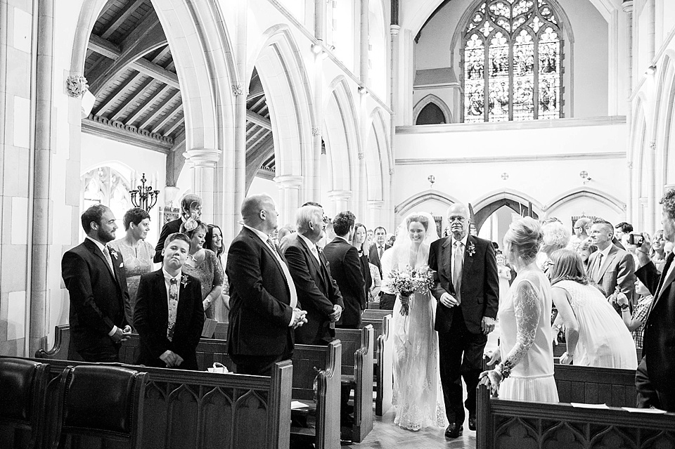 Bride and her father walk down the aisle together in church wedding ceremony - natural wedding photography by Fiona Kelly