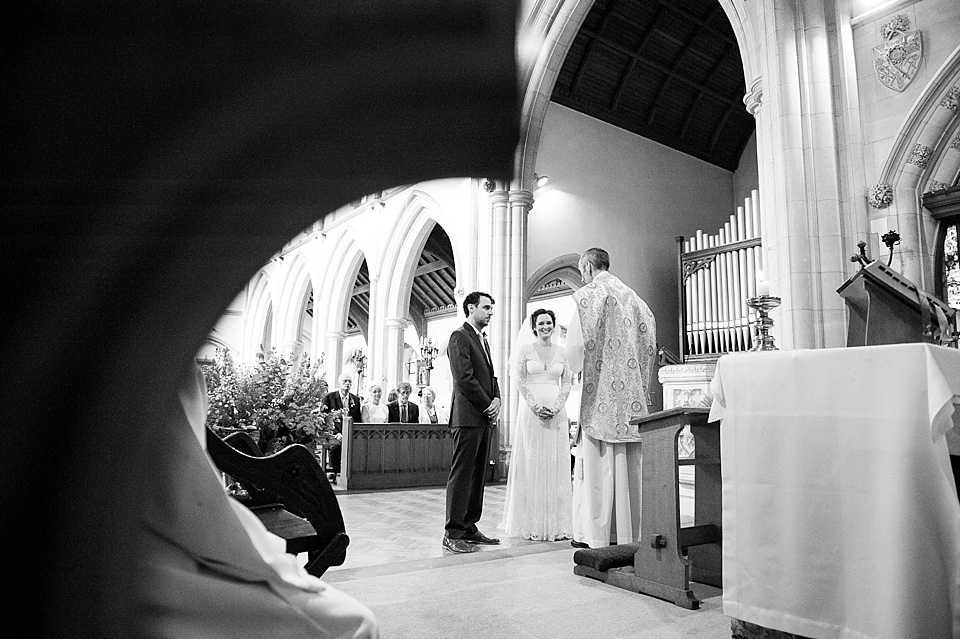 Bride and groom stand in church wedding ceremony - natural wedding photography by Fiona Kelly