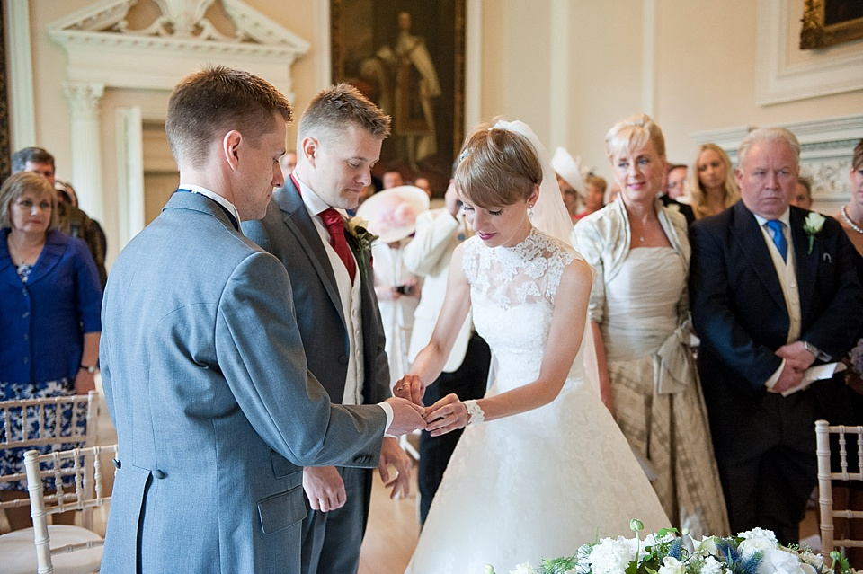Bride with short hair and traditional lace wedding dress giving groom his wedding ring - natural wedding photography by Fiona Kelly