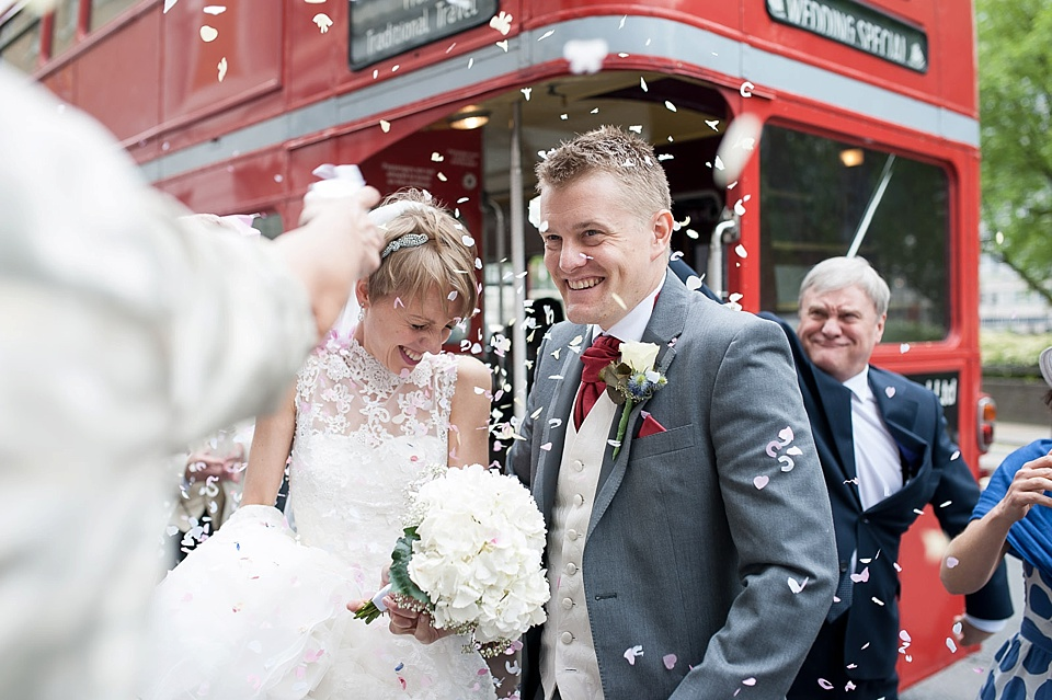 Confetti shot over bride with short hair and lace wedding dress, white hydrangea bouquet and groom in red tie standing next to London bus - natural wedding photography by Fiona Kelly
