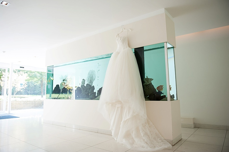 Big tulle white wedding dress hanging on fishtanks at minimalist venue - the tradition of the wedding veil and white wedding dress - natural wedding photographer - Fiona Kelly