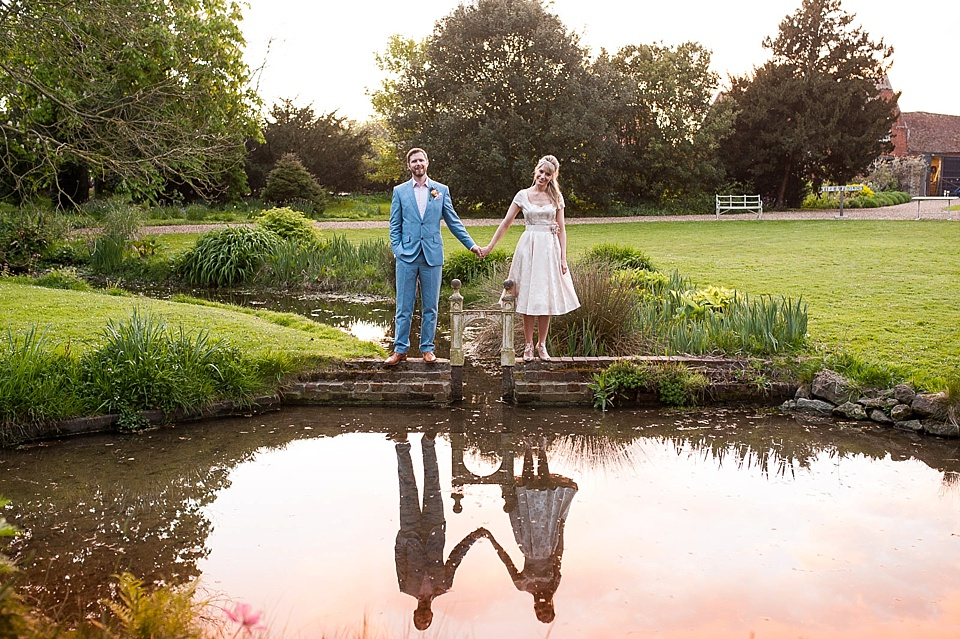 Modern wedding photography - Bride in short satin wedding dress standing with groom in blue suit - The tradition of the wedding veil and white wedding dress - natural wedding photographer - Fiona Kelly
