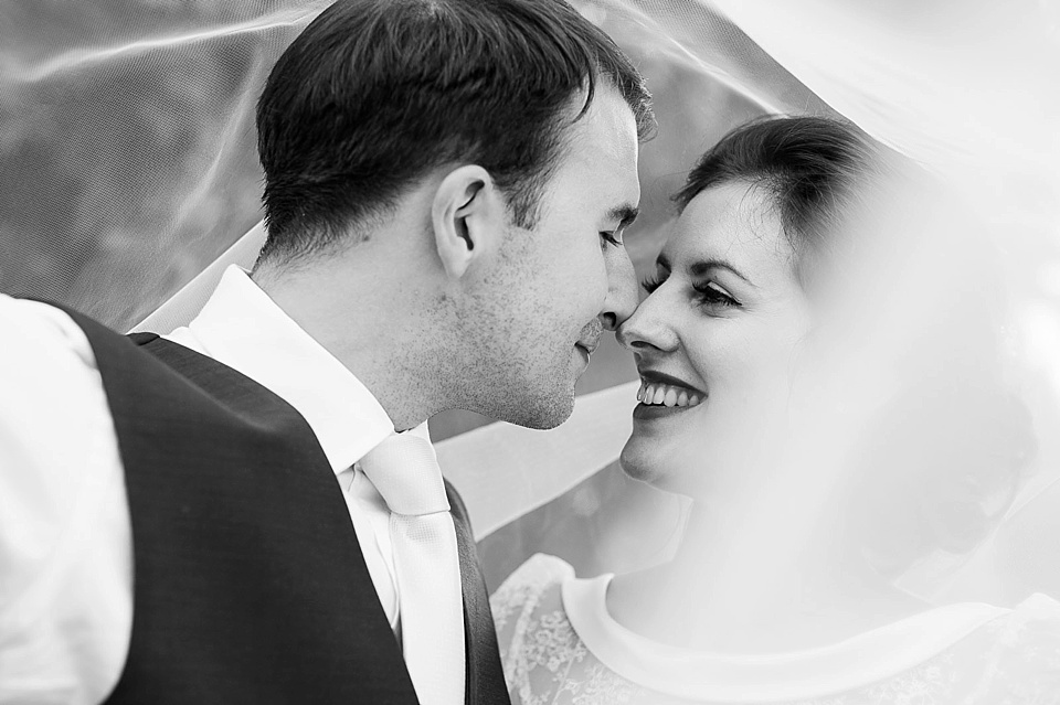Bride and groom kissing under wedding veil - The tradition of the wedding veil and white wedding dress - black and white creative wedding portrait by Fiona Kelly wedding photographer