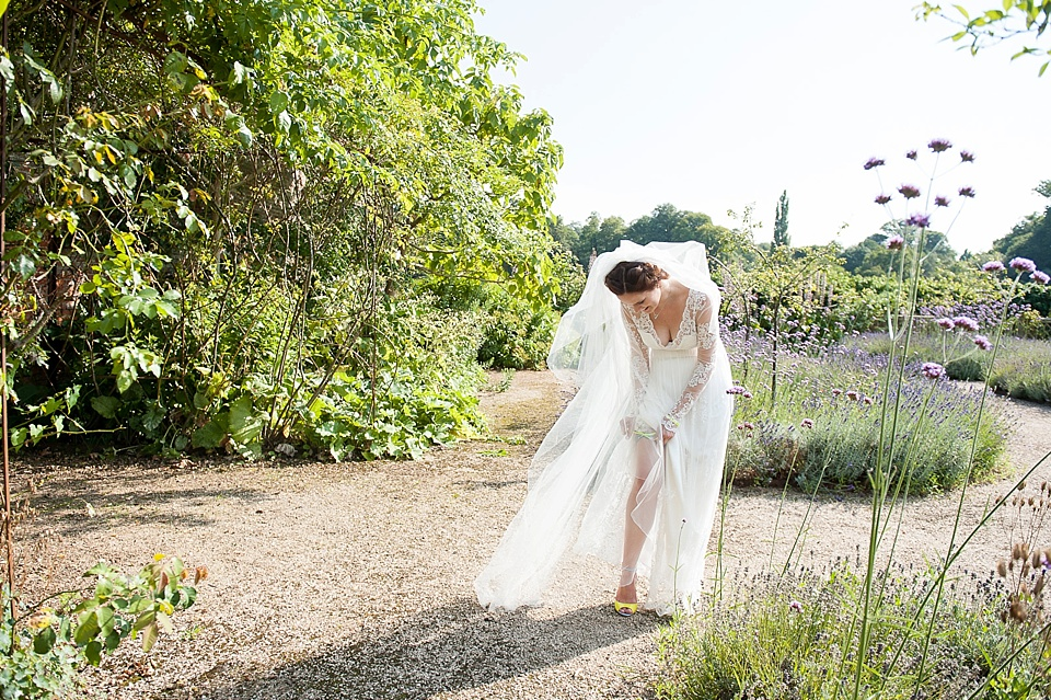 Bride putting on crochet garter - modern wedding photography - the tradition of the wedding veil and white wedding dress - natural wedding photographer - Fiona Kelly