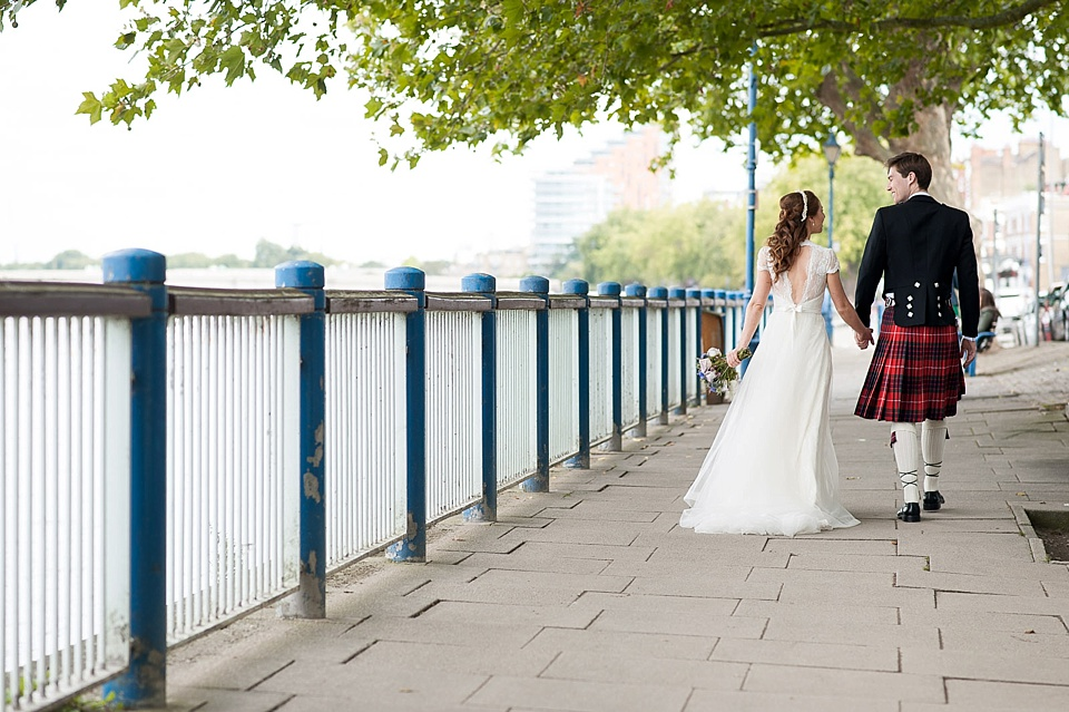 Bride with backless dress walking with groom in Scottish kilt - natural wedding photography by Fiona Kelly London wedding photographer