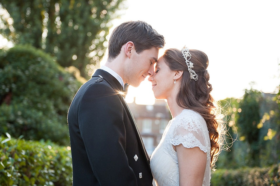 Magic golden hour - Bride with floral headpiece and short lace sleeves stands with groom in blue blazer - The tradition of the wedding veil and white wedding dress - natural wedding photographer - Fiona Kelly