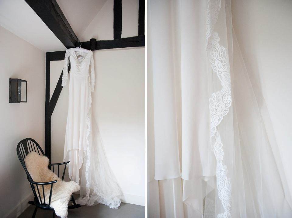 Elegant slim fitted white wedding dress hanging from wooden beam with lace edged veil - The tradition of the wedding veil and white wedding dress - Fiona Kelly wedding photographer
