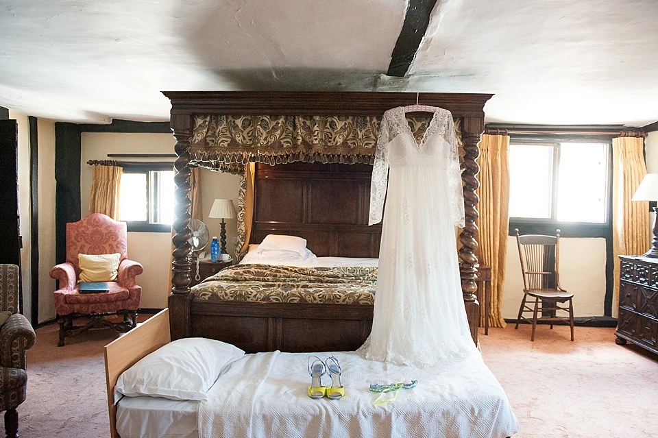 Lace sleeve wedding dress hanging on four poster bed - The tradition of the wedding veil and white wedding dress - natural wedding photographer - Fiona Kelly
