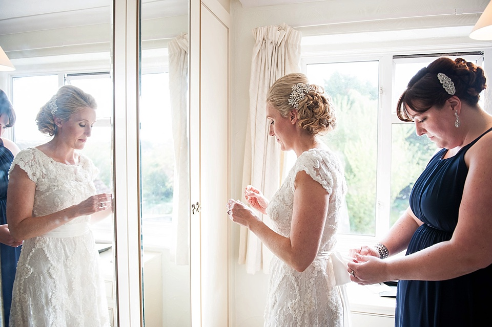 Ivory lace wedding dress - bride getting ready with bridesmaid - The tradition of the wedding veil and white wedding dress - natural wedding photographer - Fiona Kelly