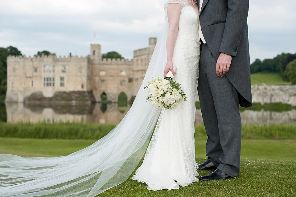 The tradition of the wedding veil and white wedding dress - wedding portrait of bride and groom at Leeds Castle by Fiona Kelly natural wedding photographer