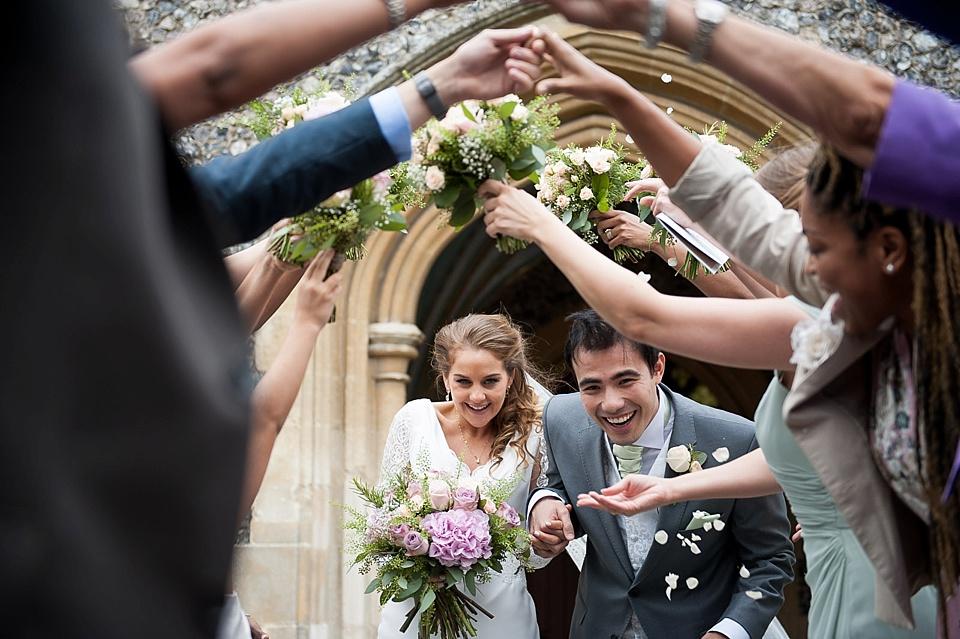 bride and groom walk under flowers_0020