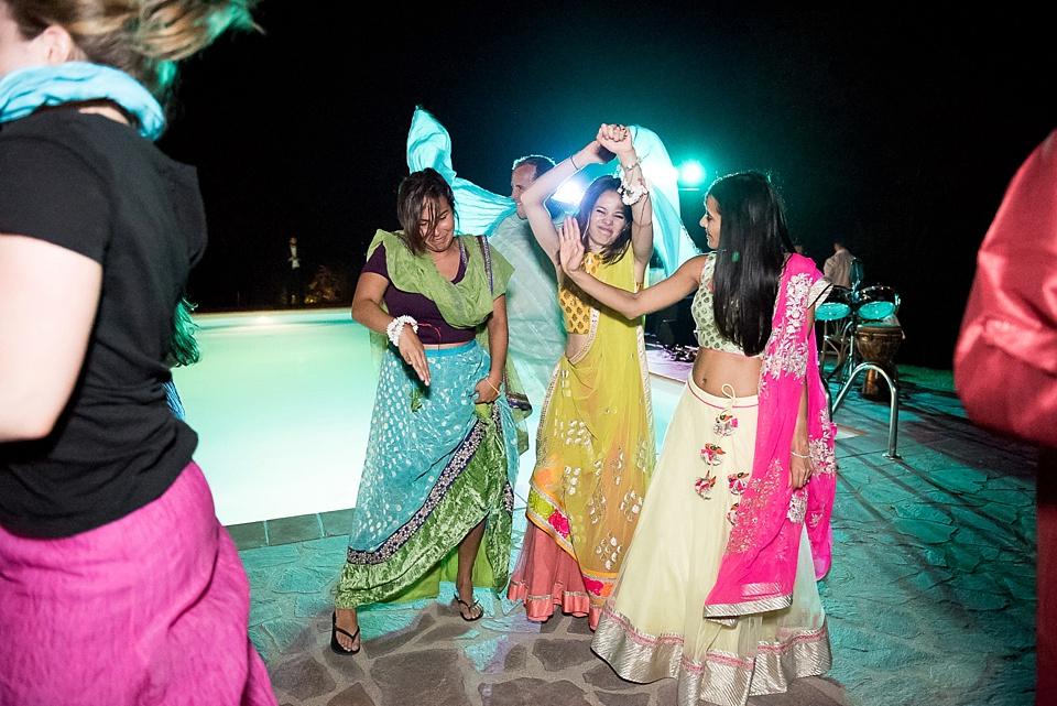 Women in colourful saris dancing at Tuscany wedding
