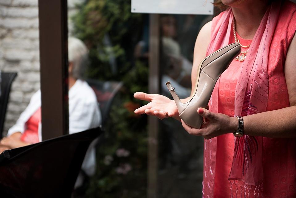 87 Woman holding shoe at wedding