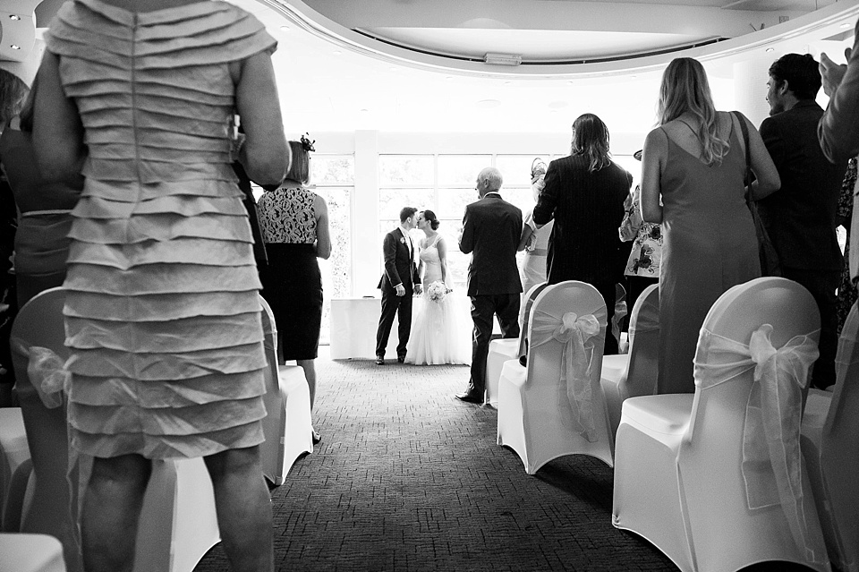 Bride and groom kiss as guests clap