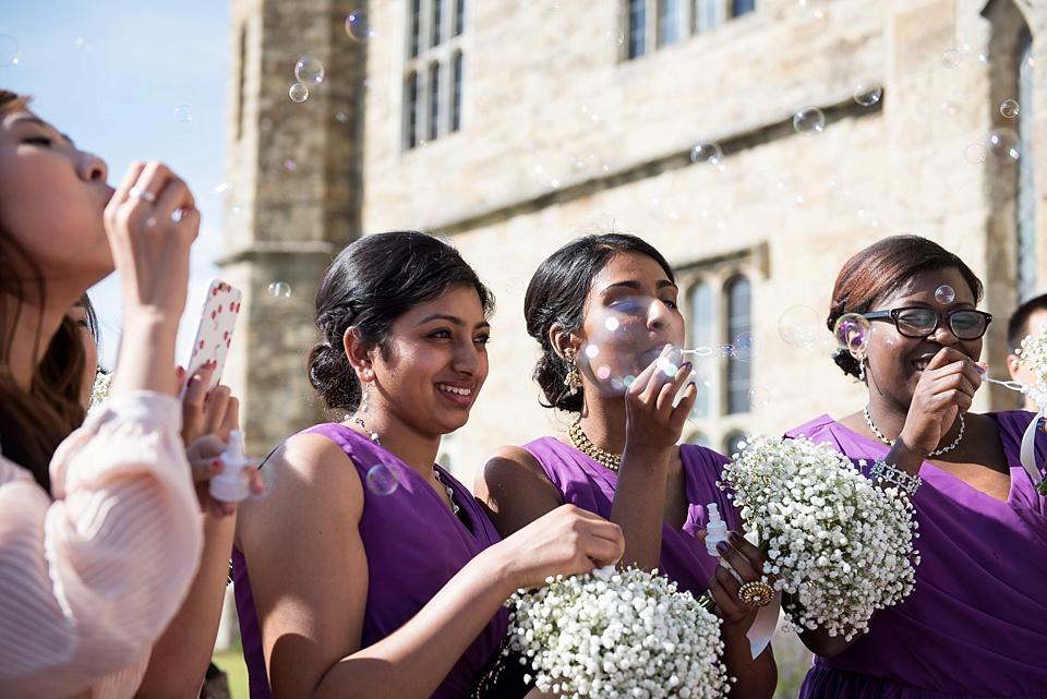 Purple bridesmaids blow bubbles