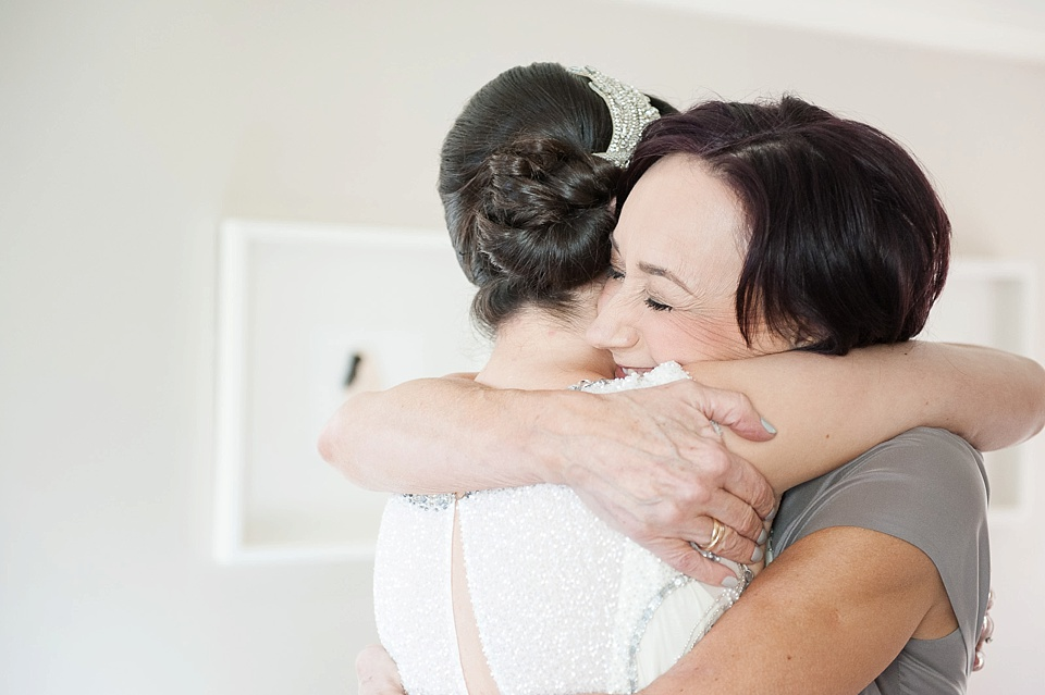 Bridesmaid and bride embrace