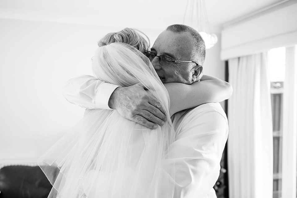 Bride and father share a hug