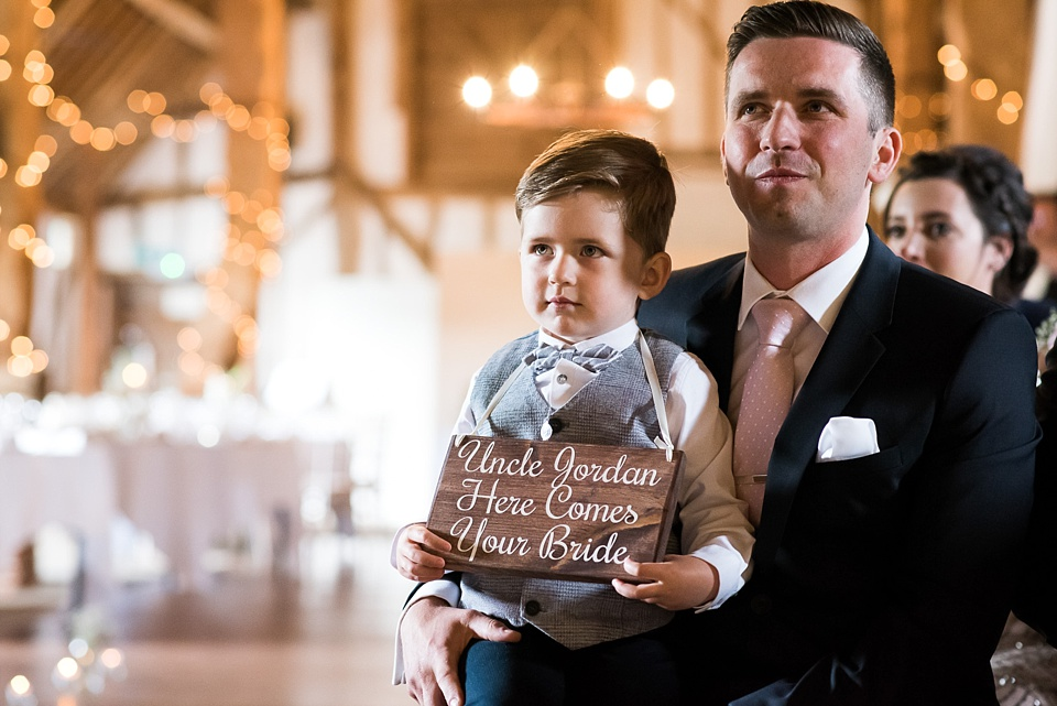 Cute page boy with here comes the bride sign Pledgdon barn Essex