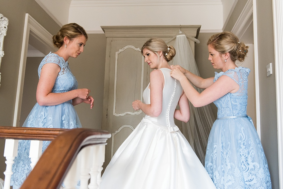 Bridesmaids helping bride into wedding dress Fetcham Park wedding