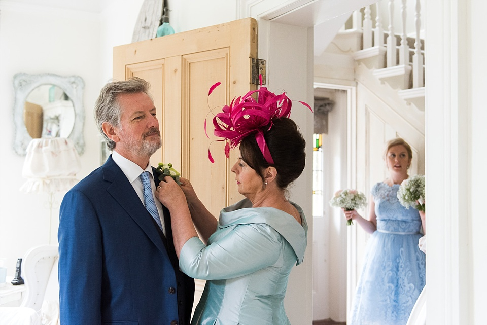 Father of the bride wearing hot pink fascinator pre-wedding morning Fetcham Park