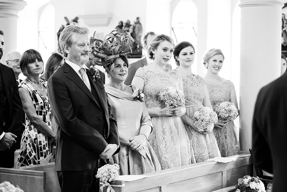 Mother, Father of the bride with bridesmaids watch church wedding ceremony