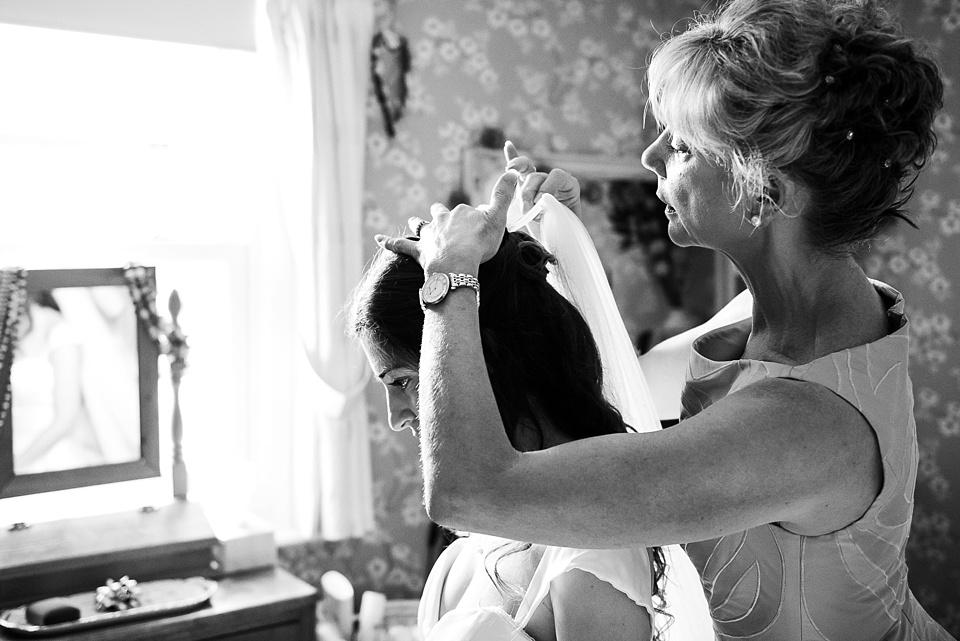 Mother placing veil on bride pre-wedding morning prep Surrey