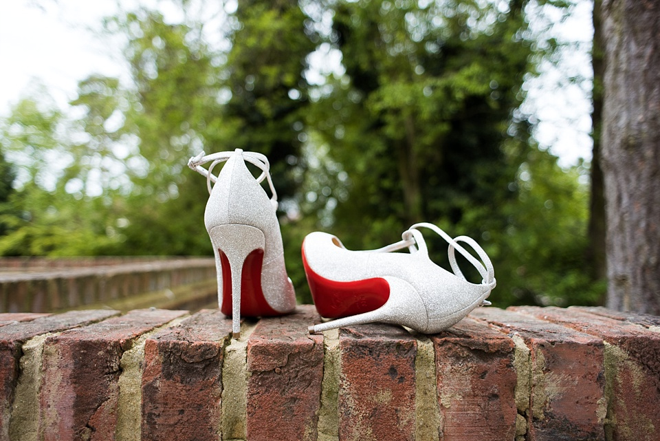 White stiletto bridal shoes on wall Essex wedding photography