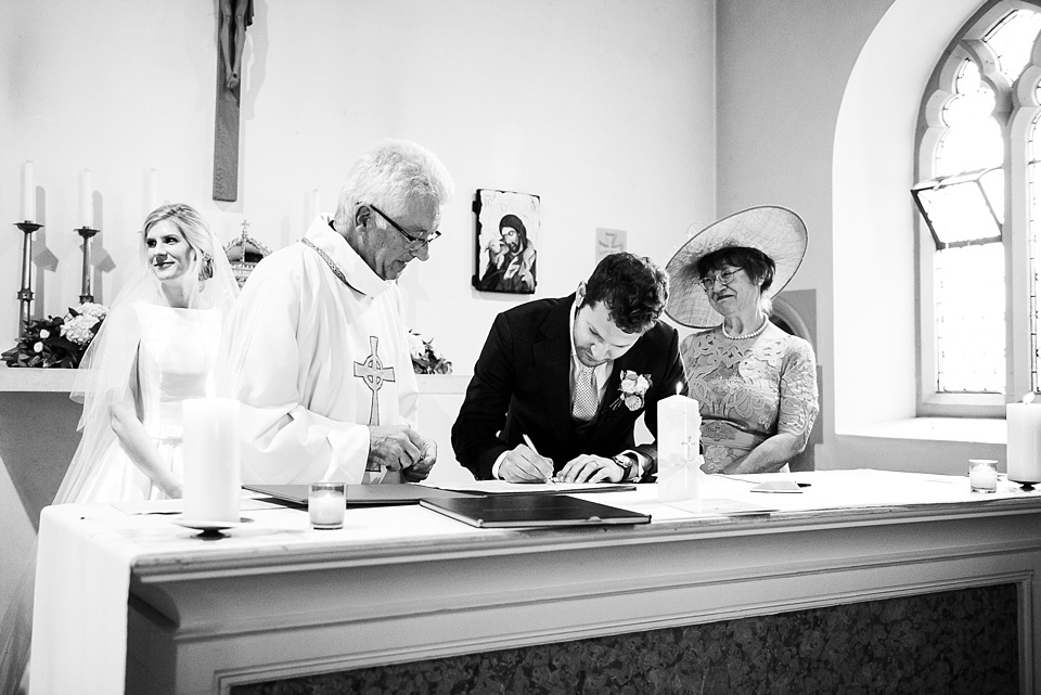 Groom signs the register Fetcham Park wedding