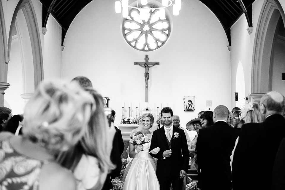 Bride with groom walk down church aisle married