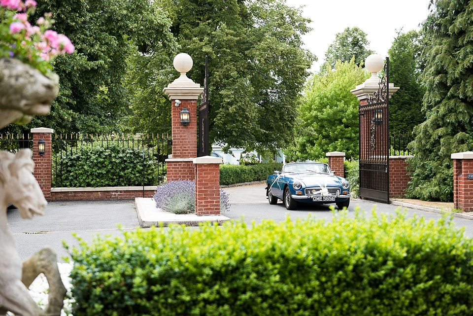 Vintage wedding car arrives at Fetcham Park Surrey