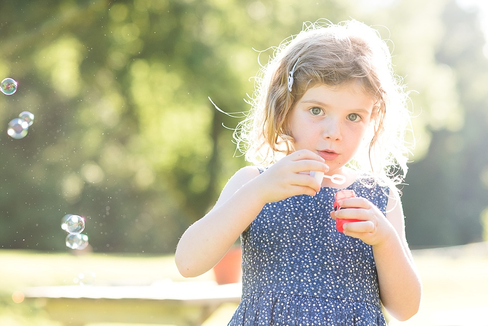 Girl blowing bubbles at summer wedding photography Surrey