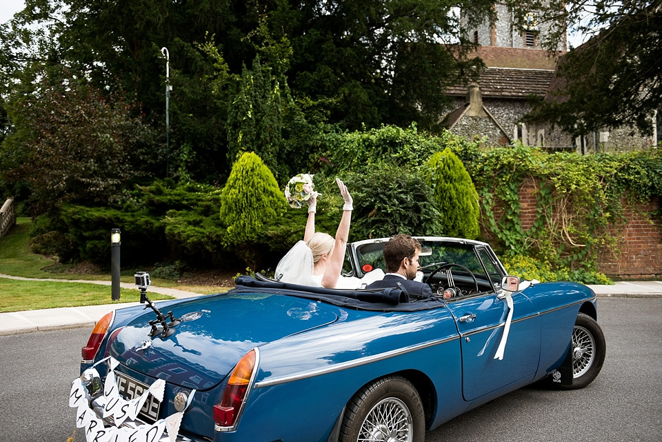 Bride and groom drive away in vintage car Surrey wedding