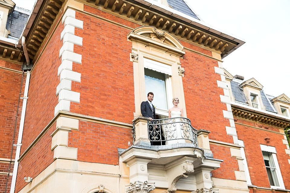 Bride and groom on balcony of Fetcham Park wedding