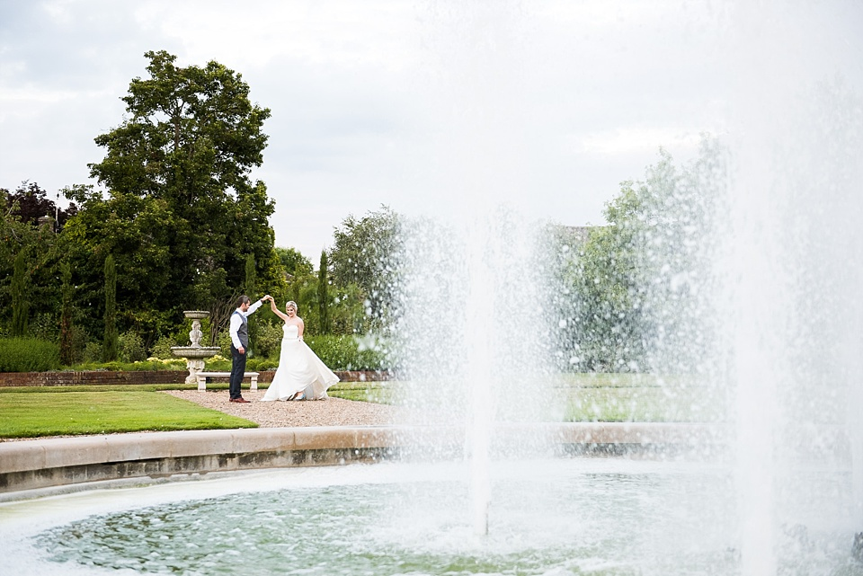 Creative wedding portrait with fountain at Fetcham Park wedding venue Surrey