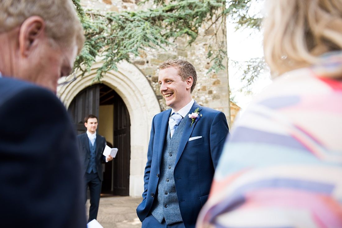Laughing groom outside church Associate Wedding Photographer