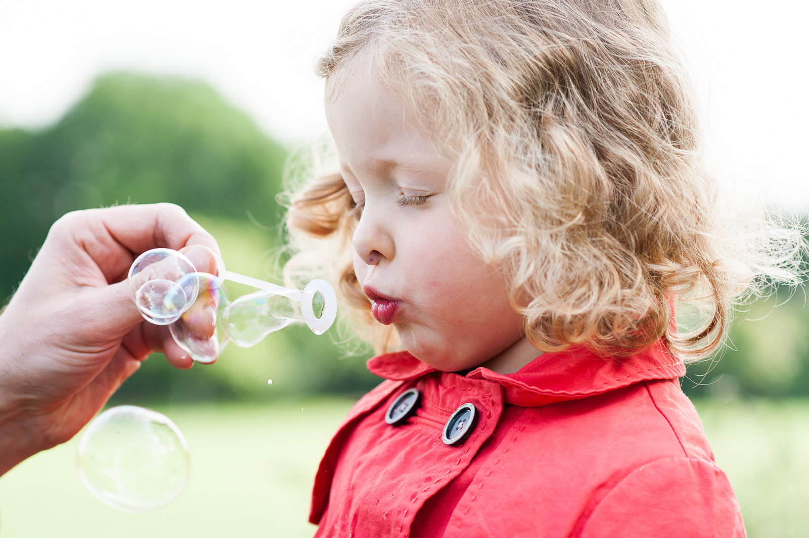 Little girl blowing bubbles creative family photographer Surrey