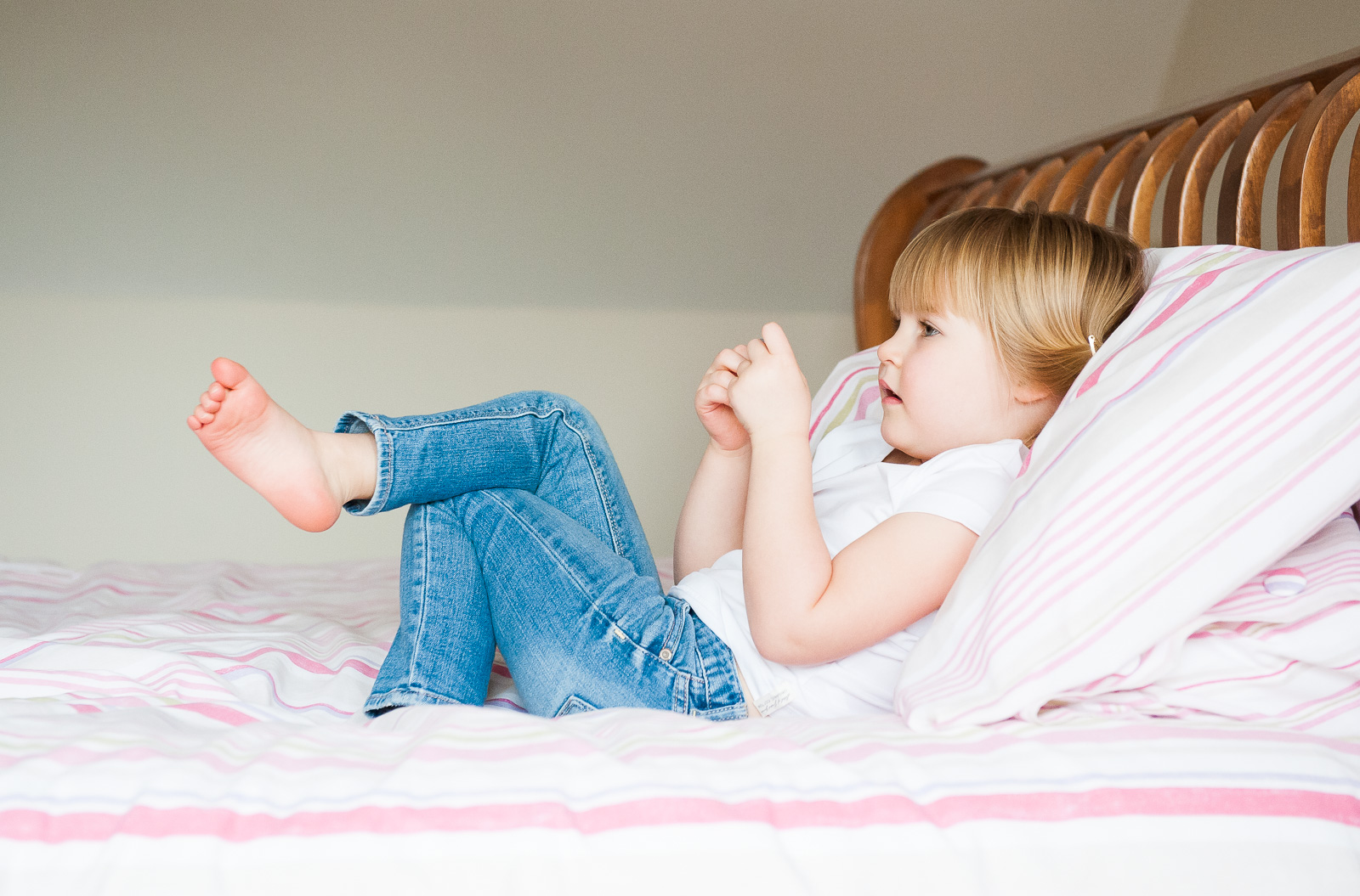 Cute girl relaxes on bed family photography London