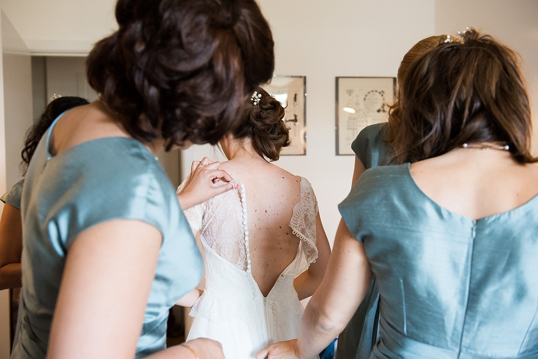 Bridesmaids helping bride Associate Wedding Photographer