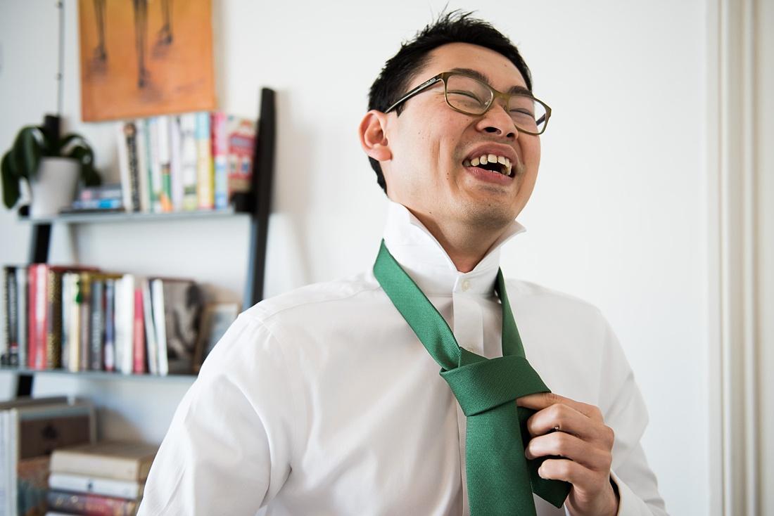 Giggling best man wearing green tie pre wedding photography London
