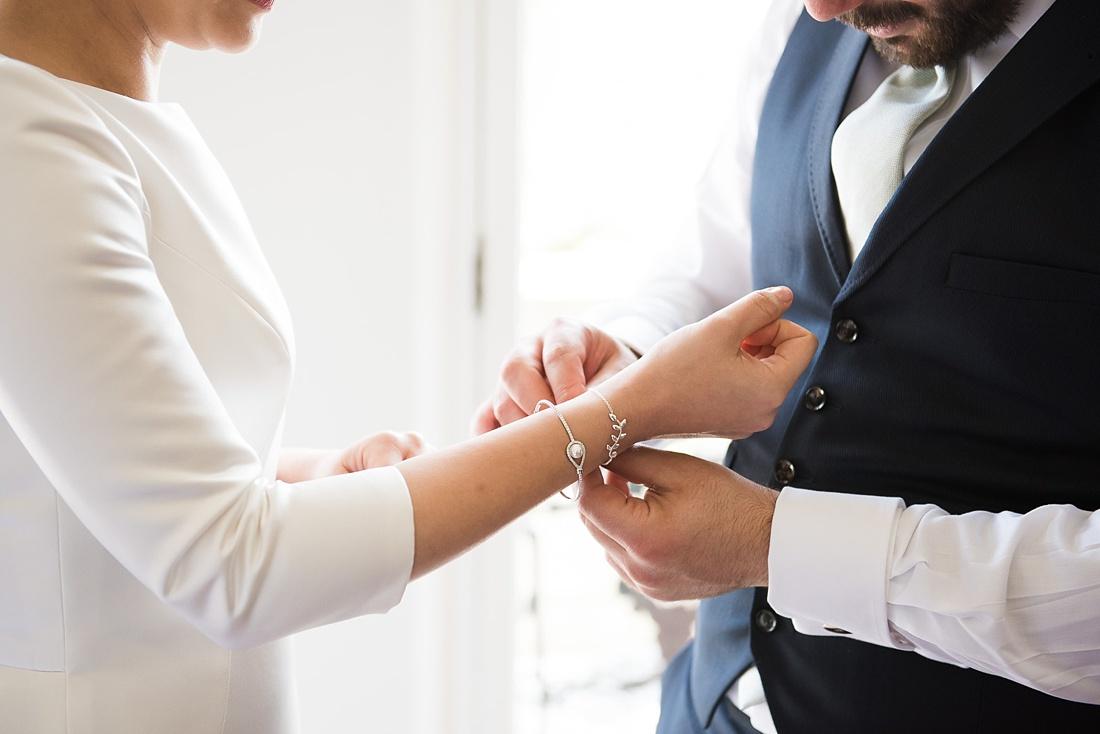 Groom places delicate silver bracelet on bride London wedding