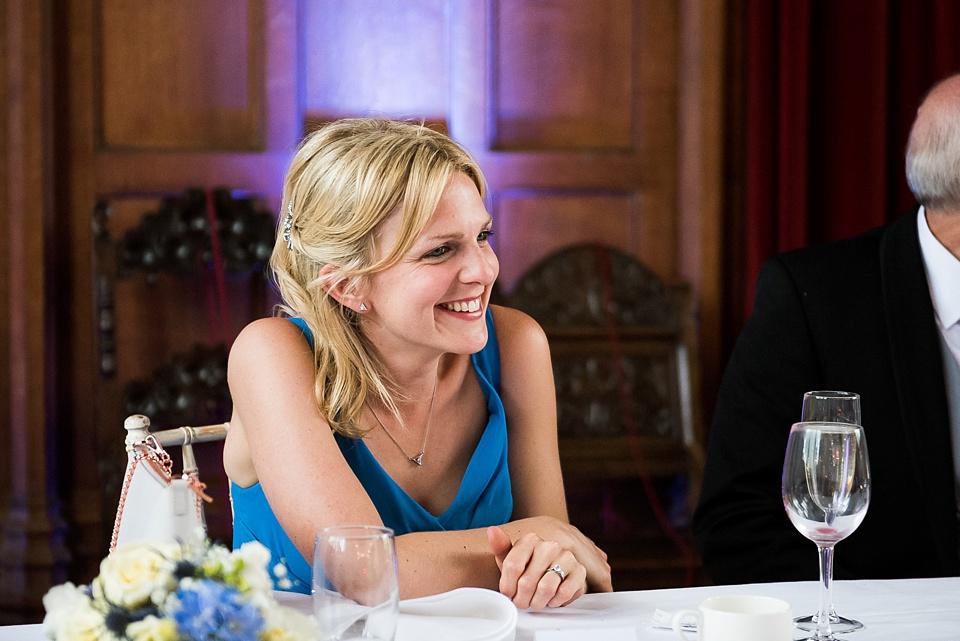 Bridesmaid smiles wearing Kenneth Winston blue dress London wedding