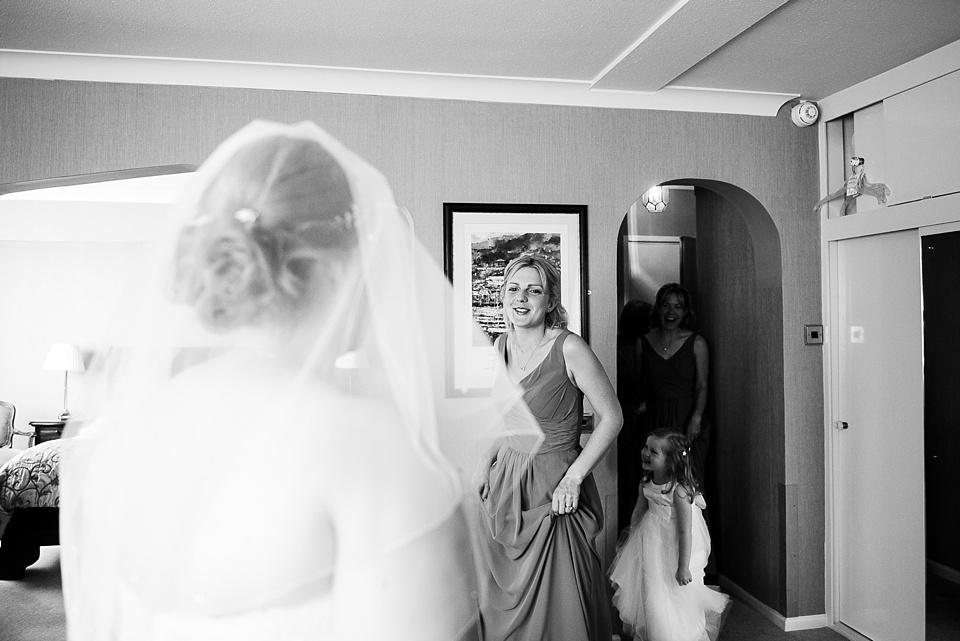 Bridesmaid admires bride pre wedding morning photography London
