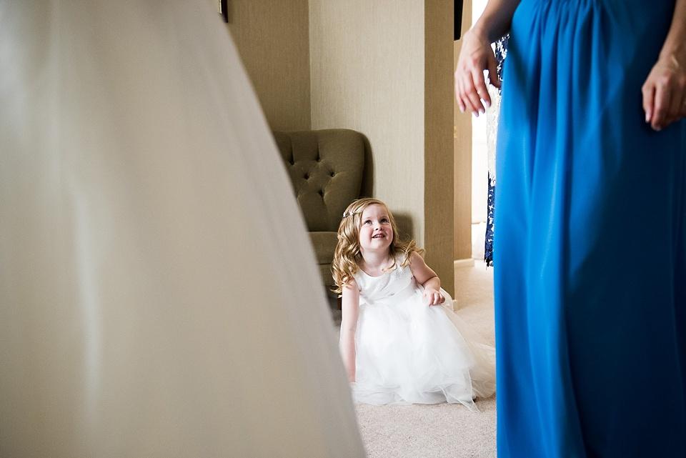 Flower girl admires bridesmaid London family wedding