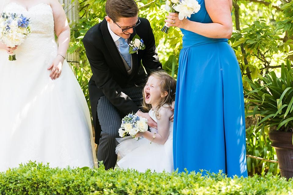 Flower girl giggling at family wedding Eltham Palace London
