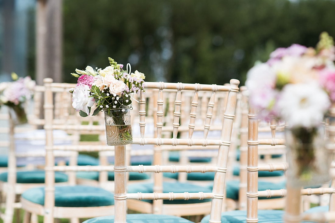 Outdoor wedding ceremony with chair flower design by Larkspur Floral Design